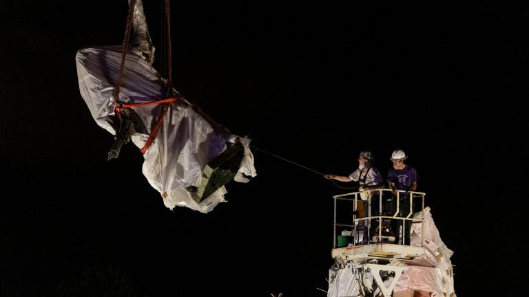 City municipal crews help guide the Christopher Columbus statue in Grant Park as it is removed by a crane, Friday, July 24, 2020, in Chicago. A statue of Christopher Columbus that drew chaotic protests in Chicago was taken down early Friday amid a plan by President Donald Trump to dispatch federal agents to the city. (Tyler LaRiviere / Chicago Sun-Times via AP)