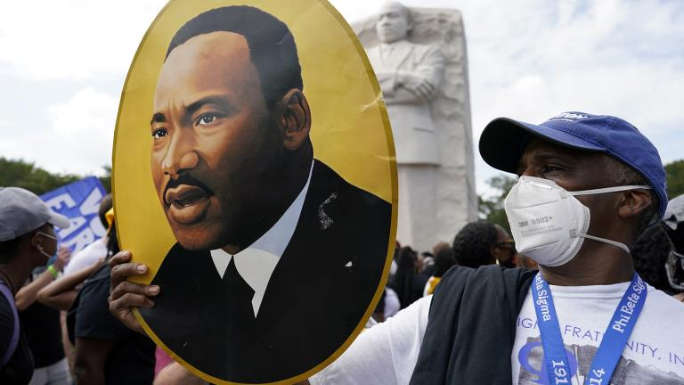A man holds a photo of Martin Luther King, Jr., at the Martin Luther King Jr. Memorial during the March on Washington, Friday Aug. 28, 2020, in Washington. (AP Photo / Carolyn Kaster)