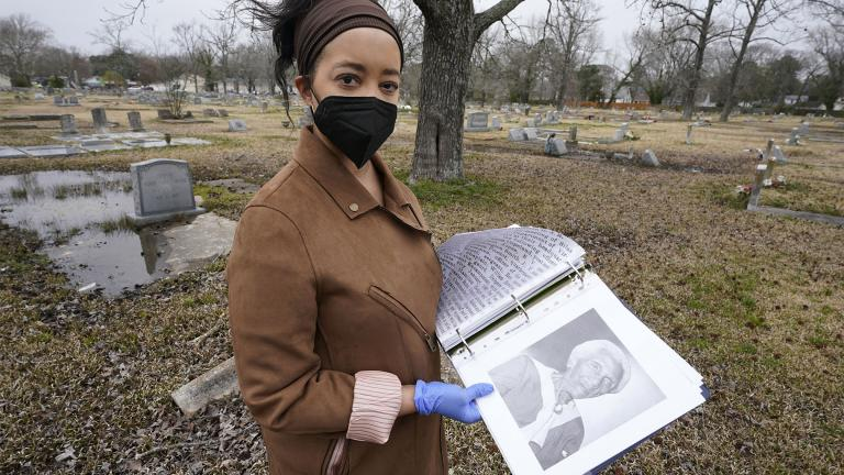 Nadia Orton, a genealogist and family historian in Virginia, opens a binder of research next to the grave of a Civil War era slave at the Lincoln Memorial Cemetery in Portsmouth, Va., Tuesday, March 23, 2021. Orton has worked tracing her own family and others to historically Black cemeteries. (AP Photo / Steve Helber)
