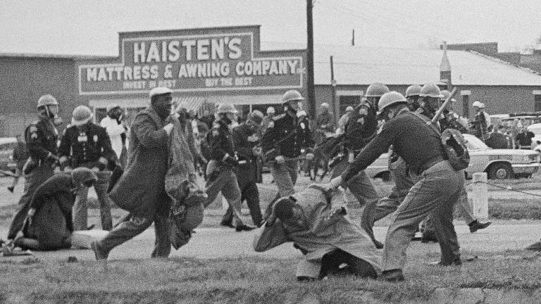 In this March 7, 1965, file photo, a state trooper swings a billy club at John Lewis, right foreground, chairman of the Student Nonviolent Coordinating Committee, to break up a civil rights voting march in Selma, Ala. (AP Photo / File)