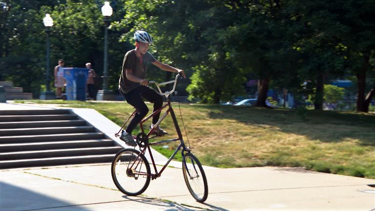 Malcolm Langford, 14, rides a tall bike at a Logan Square Park meetup organized by the custom bike club Rat Patrol on June 11. (WTTW News)