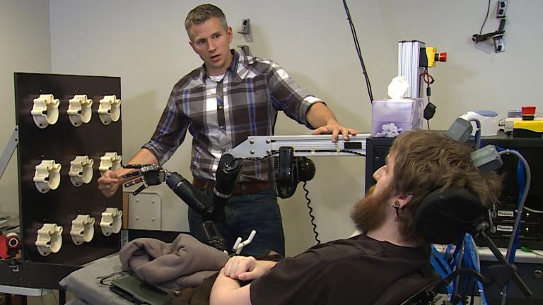 Rob Gaunt from the University of Pittsburgh prepares Nathan Copeland, who was paralyzed in 2004, for a brain computer interface sensory test using a robotic arm. (UPMC / Pitt Health Sciences Media Relations)
