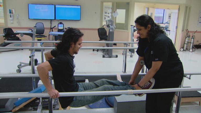Jonathan Annicks works with staff at Schwab Rehabilitation Hospital. (WTTW News)