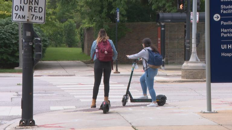 In this file photo, riders use electric scooters on the campus of the University of Illinois at Chicago. The city started its four-month scooter pilot program in June 2019. (WTTW News)