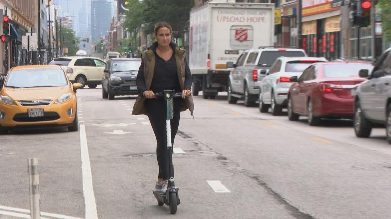 A woman rides a scooter in Chicago during the city's first pilot program in 2019. (WTTW News)