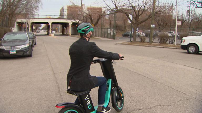 """Chicago Tonight"" producer Nick Blumberg tests a seated electric scooter. (WTTW News)"