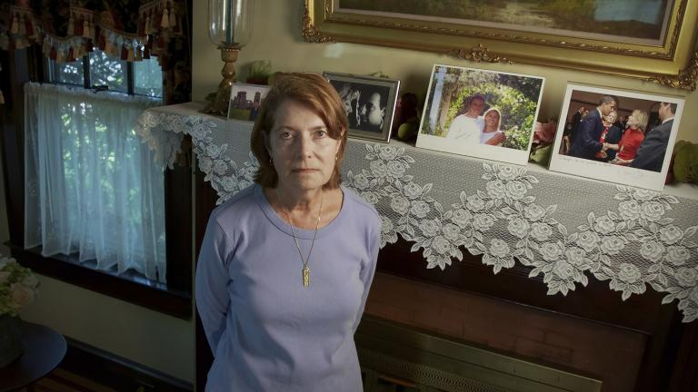 Margot Eckert stands by a display of pictures of her brother-in-law Sean Rooney and sister Beverly Eckert at her home, Thursday, July 15, 2021, in Springfield, Mass. (AP Photo / Robert Bumsted)