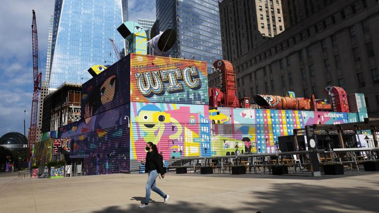 A woman walks by the colorful murals that surround the foundation for 2 World Trade Center, Wednesday, Sept. 8, 2021 in New York. (AP Photo / Mark Lennihan)