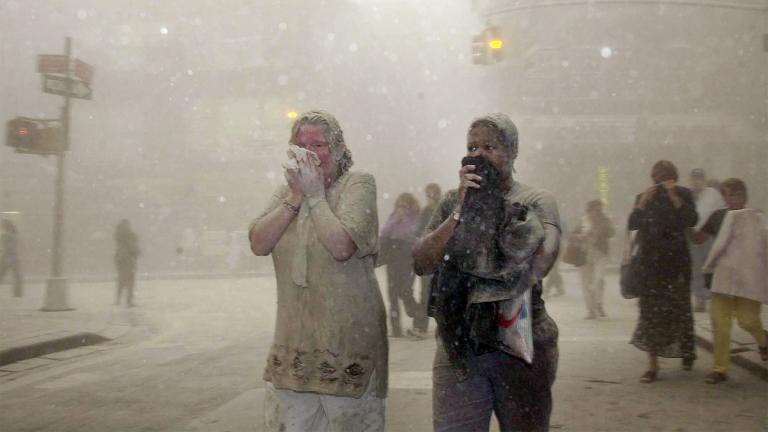 In this Sept. 11, 2001 file photo, people covered in dust from the collapsed World Trade Center buildings, walk through the area, in New York. (AP Photo / Suzanne Plunkett, File)