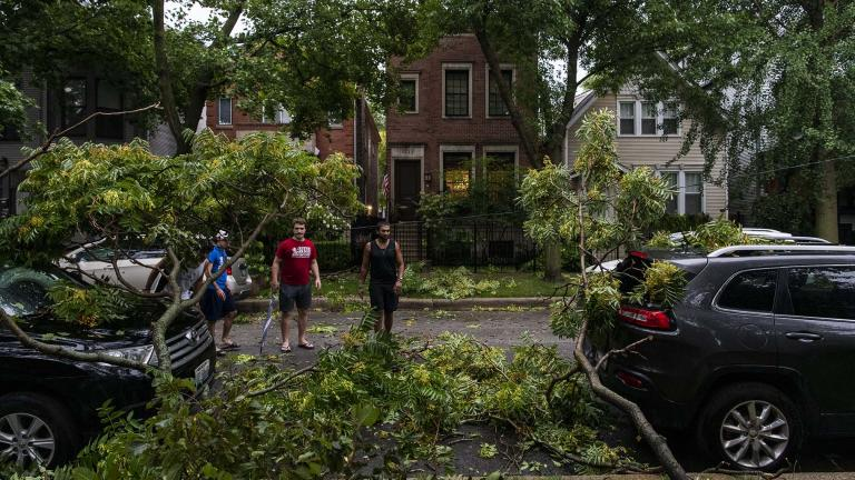 A group of neighbors surveys the damage to vehicles on their block after a severe thunderstorm battered Chicago neighborhoods, Monday, Aug. 10, 2020. (Tyler LaRiviere / Sun-Times / Chicago Sun-Times via AP)