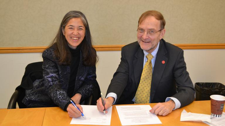 Chicago Department of Public Health commissioner Dr. Julie Morita and UIC School of Public Health Dean Dr. Paul Brandt-Rauf sign an agreement formalizing the yearslong partnership between the two organizations. (UIC School of Public Health)
