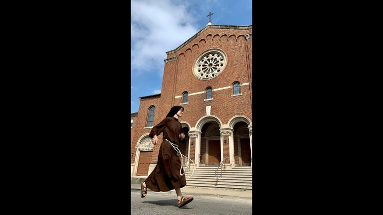 Sister Stephanie Baliga runs past the Our Lady of the Angels church in Chicago. (Jay Shefsky / WTTW News)