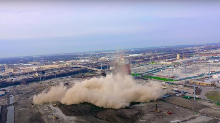 A still image from a video taken of the demolition of the Crawford Coal Plant smokestack, April 11, 2020. (Alejandro Reyes / YouTube)