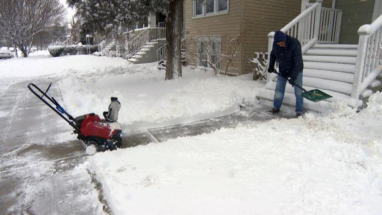 A man shovels snow after a storm in Chicago in February 2021. More snow is expected in the area on Valentine's Day, along with subzero wind chills, according to the National Weather Service. (WTTW News)