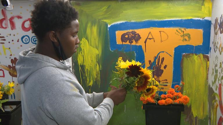 A young flower farmer creates a bouquet at Southside Blooms. (WTTW News)