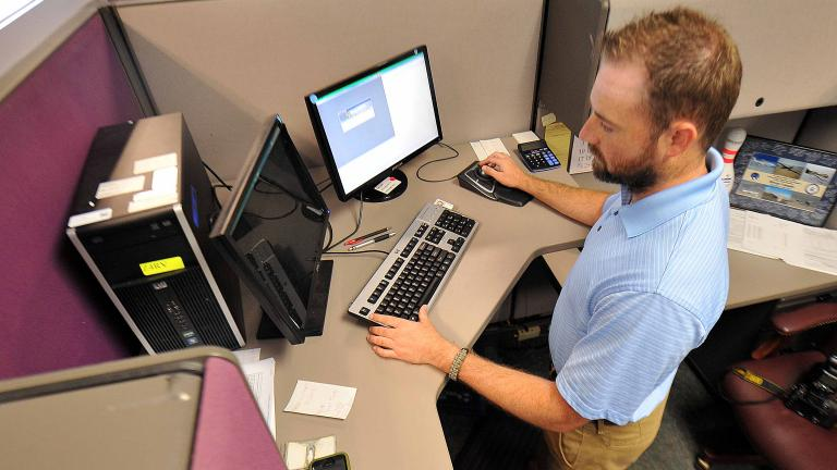 Bryan Canady, Air Force Life Cycle Management Center contracting specialist, performs his job while standing at the computer. (Tommie Horton / U.S. Air Force)