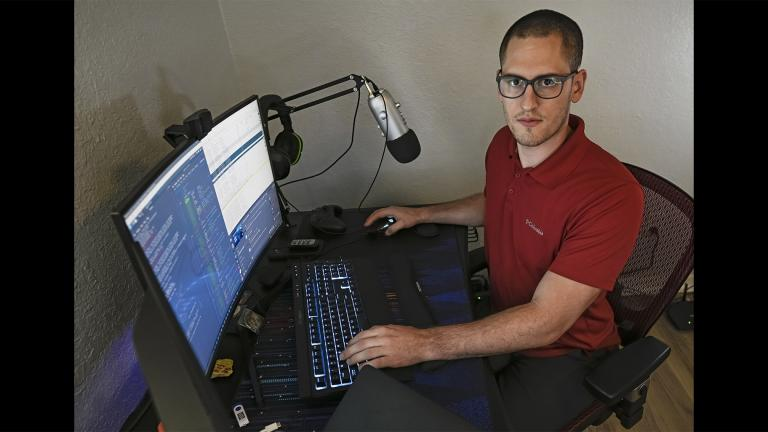 In this Sept. 20, 2021, photo Austin Moody poses for a photo as he sits a his home work station in Tampa, Fla. (AP Photo / Steve Nesius)