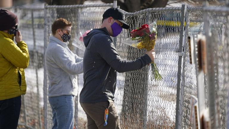 Kiefer Johnson places a bouquet of flowers into a makeshift fence put up around the parking lot outside a King Soopers grocery store where a mass shooting took place a day earlier, in Boulder, Colo., Tuesday, March 23, 2021. (AP Photo / David Zalubowski)