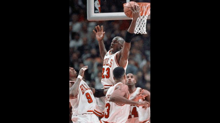 In this June 10, 1998, file photo, Chicago Bulls' Michael Jordan reaches high above teammates Dennis Rodman, left, Scottie Pippen, and Scott Burrell (24) for a rebound against the Utah Jazz in the second half of Game 4 in the NBA Finals in Chicago. (AP Photo / Michael S. Green, File)