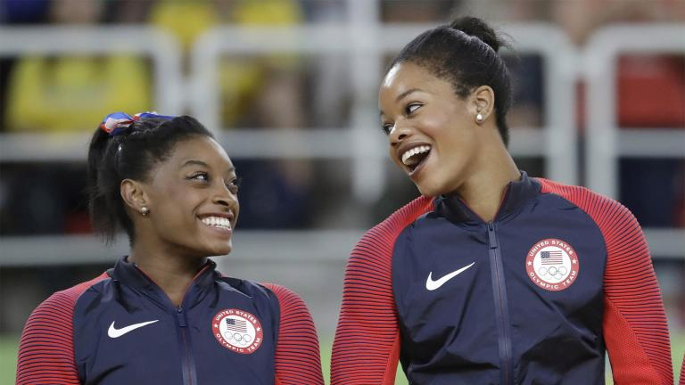 FILE - In this Aug. 9, 2016, file photo, U.S. gymnasts and gold medallists, Simone Biles, left and Gabrielle Douglas celebrate on the podium during the medal ceremony for the artistic gymnastics women's team at the 2016 Summer Olympics in Rio de Janeiro, Brazil. (AP Photo/Julio Cortez, File)