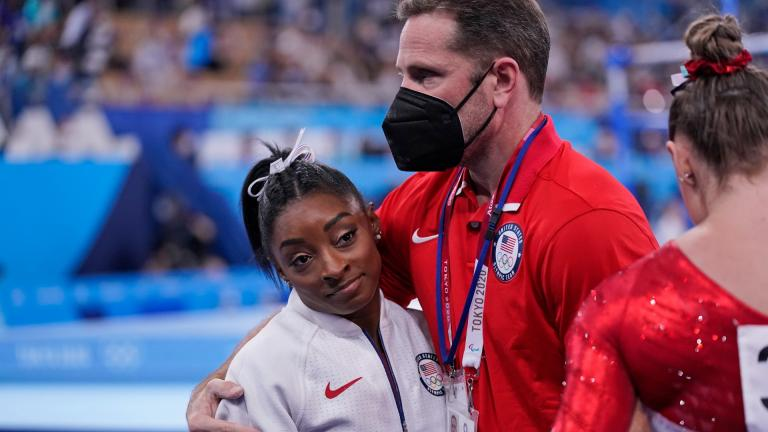 Coach Laurent Landi embraces Simone Biles, after she exited the team final with apparent injury, at the 2020 Summer Olympics, Tuesday, July 27, 2021, in Tokyo. (AP Photo / Gregory Bull)