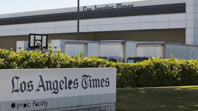 Delivery trucks are parked outside the Los Angeles Times Olympic Facility in Los Angeles, Sunday, Dec. 30, 2018. A computer virus hit the newspaper printing plant in Los Angeles, and at Tribune Publishing newspapers across the country. (AP Photo / Damian Dovarganes)