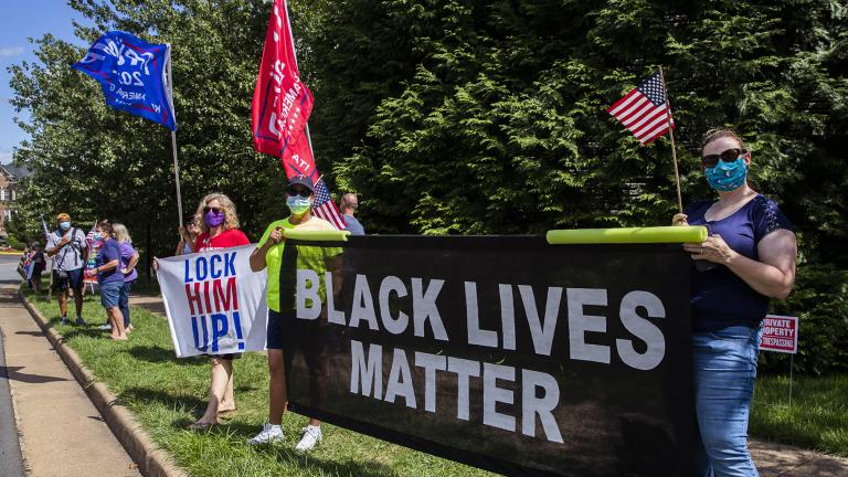 Supporters of President Donald Trump and protesters hold banners as they wait for the motorcade of President Trump outside the Trump National Golf Club in Sterling, Va., Sunday, Aug. 30, 2020. (AP Photo / Manuel Balce Ceneta)