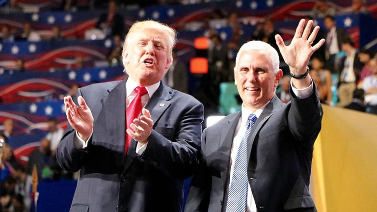 Republican presidential nominee Donald Trump and vice presidential nominee Gov. Mike Pence greet the crowd at the front of the stage. (Evan Garcia / Chicago Tonight)