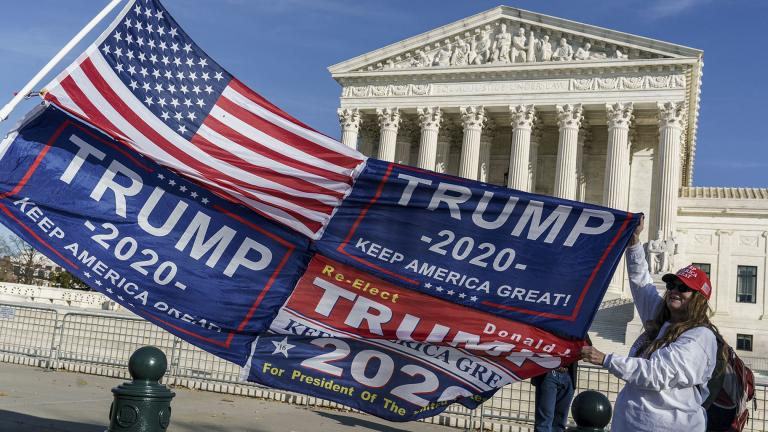 Kathy Kratt of Orlando, Fla., displays her Trump flags as she and other protesters demonstrate their support for President Donald Trump at the Supreme Court in Washington, Friday, Dec. 11, 2020. (AP Photo / J. Scott Applewhite)