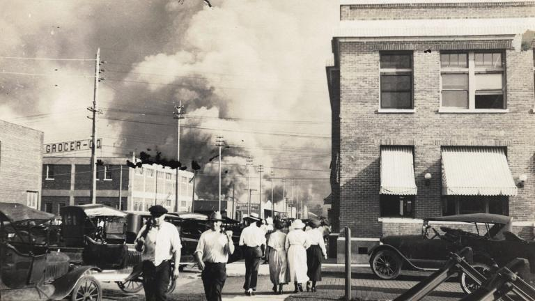 In this photo provided by Department of Special Collections, McFarlin Library, The University of Tulsa, two armed men walk away from burning buildings as others walk in the opposite direction during the June 1, 1921, Tulsa Race Massacre in Tulsa, Okla. (Department of Special Collections, McFarlin Library, The University of Tulsa via AP, File)