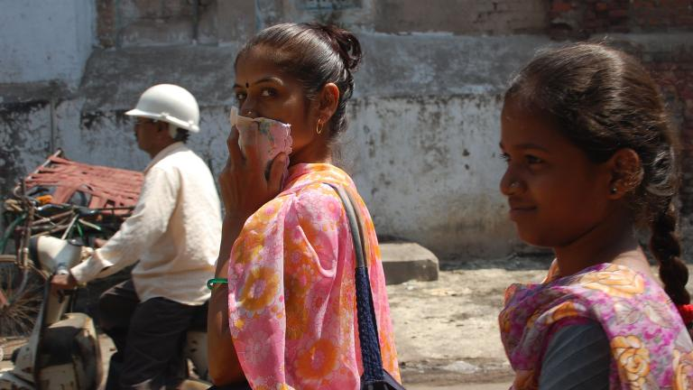 A woman covers her mouth with a handkerchief while walking through the streets of Ahmedabad, India. (Jill Ryan / WBUR Boston's NPR News Station / Flickr)