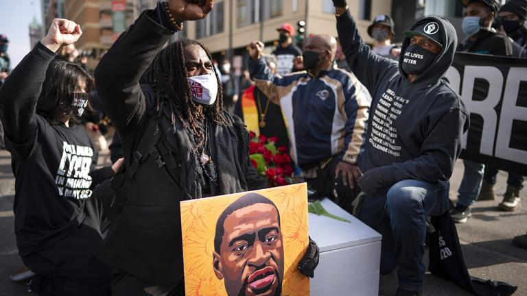 Cortez Rice, left, of Minneapolis, sits with others in the middle of Hennepin Avenue on Sunday, March 7, 2021, in Minneapolis, Minn., to mourn the death of George Floyd a day before jury selection is set to begin in the trial of former Minneapolis officer Derek Chauvin, who is charged in Floyd's death. (Jerry Holt / Star Tribune via AP)