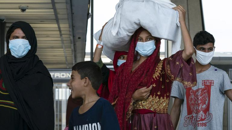 People evacuated from Kabul, Afghanistan, walk through the terminal before boarding a bus after they arrived at Washington Dulles International Airport, in Chantilly, Va., on Monday, Aug. 30, 2021. (AP Photo / Jose Luis Magana)