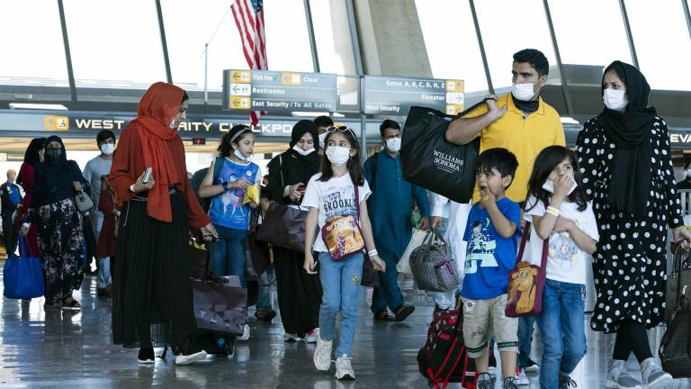 Families evacuated from Kabul, Afghanistan, walk through the terminal before boarding a bus after they arrived at Washington Dulles International Airport, in Chantilly, Va., on Thursday, Sept. 2, 2021. (AP Photo / Jose Luis Magana)