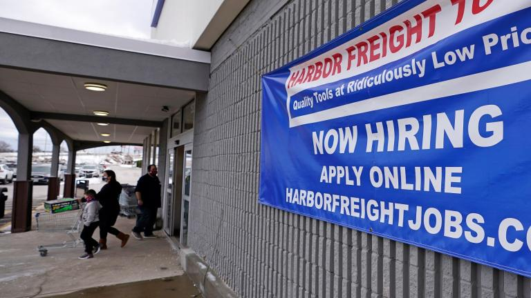"""In this Dec. 10, 2020, file photo, a """"Now Hiring"""" sign hangs on the front wall of a Harbor Freight Tools store in Manchester, N.H. (AP Photo / Charles Krupa, File)"""