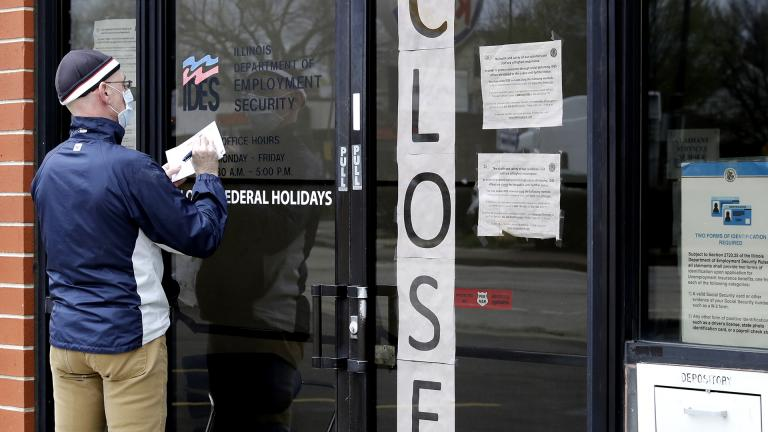 In this April 30, 2020 file photo, a man writes information in front of Illinois Department of Employment Security in Chicago. (AP Photo / Nam Y. Huh, File)