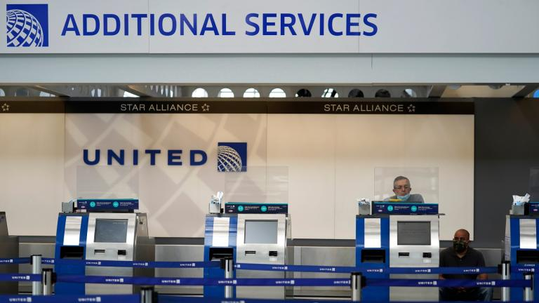 In this Oct. 14, 2020 file photo, United Airlines employees work at ticket counters in Terminal 1 at O'Hare International Airport in Chicago. (AP Photo / Nam Y. Huh, File)