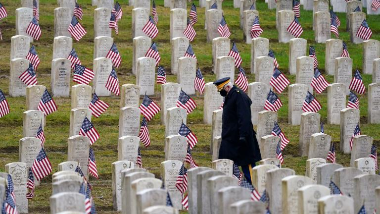 Retired U.S. Army veteran Bill MacCully walks among flag-covered graves in the Veterans Cemetery of Evergreen Washelli Memorial Park on Veterans Day, Wednesday, Nov. 11, 2020, in Seattle. (AP Photo / Elaine Thompson)
