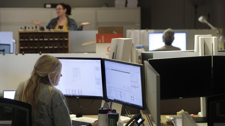 Architectural designer Erica Shannon, front, works at a computer as accounting manager Andrea Clark, top, speaks with a colleague at the design firm Bergmeyer, Wednesday, July 29, 2020, at the company's offices, in Boston.  (AP Photo / Steven Senne)