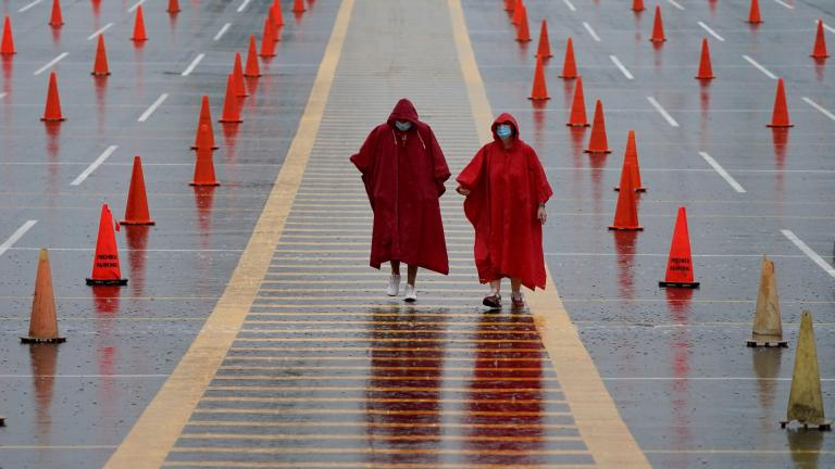 In this Aug. 29, 2020, file photo, fans walk through a parking lot at Arrowhead Stadium marked with traffic cones to keep fans from parking too close together during NFL football training camp for the Kansas City Chiefs in Kansas City, Mo. (AP Photo / Charlie Riedel, File)