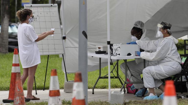 In this Friday, July 17, 2020 file photo, health care workers take information from people in line at a walk-up COVID-19 testing site during the coronavirus pandemic in Miami Beach, Fla. (AP Photo / Lynne Sladky)