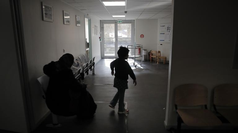 A child and his mother wait at the reception in the pediatric unit of the Robert Debre hospital, in Paris, France, Tuesday, March 2, 2021. (AP Photo/Christophe Ena)