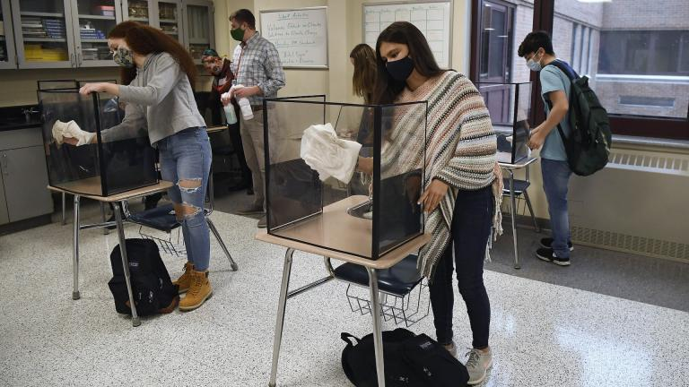 In this March 18, 2021, file photo, students in teacher Christopher Duggan's science class clean their work areas at the end of class at Windsor Locks High School in Windsor Locks, Conn. (AP Photo/Jessica Hill, File)