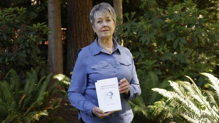 Karen McKnight stands in her backyard on Saturday, June 19, 2021, in Sammamish, Wash., holding two books written by her brother Ross Bagne of Cheyenne, Wyo. Nearly all COVID-19 deaths in the United States now are in people who weren't vaccinated, like Bagne, a staggering demonstration of how effective the vaccines have been (AP Photo / John Froschauer)