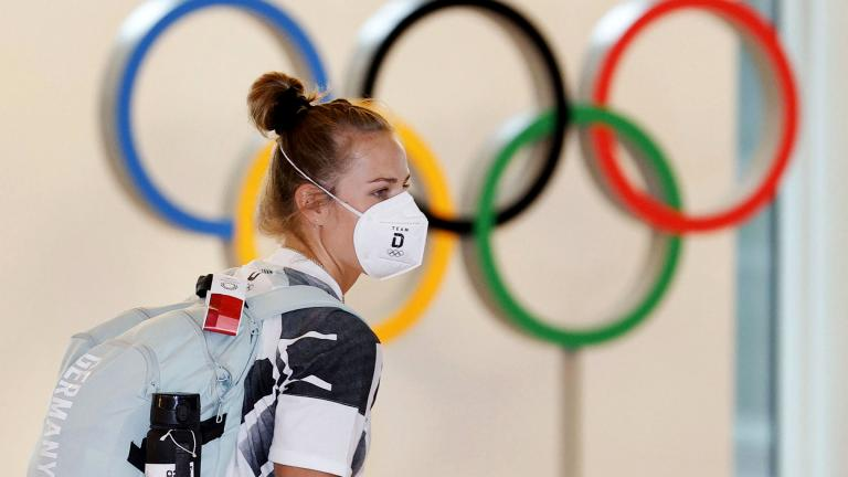 A German athlete, wearing face mask, walks past the Olympic rings display on their arrival at Haneda airport in Tokyo, Thursday, July 1, 2021. (Kyodo News via AP)