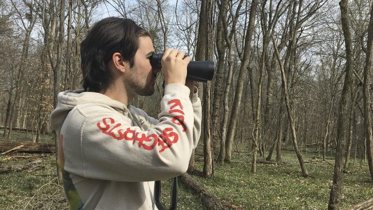 In this March 24, 2020 photo, provided by Conner Brown, he is seen using binoculars to look for birds in Cedar Island, Maryland. (Elizabeth Wright / Courtesy of Conner Brown via AP)