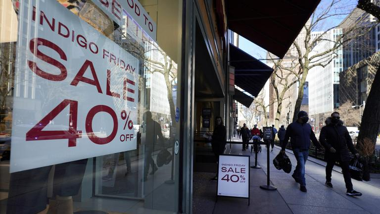 Shoppers pass an Indigo Friday 40% Off sign Saturday, Nov. 28, 2020, on Chicago's famed Magnificent Mile shopping district. (AP Photo / Charles Rex Arbogast)