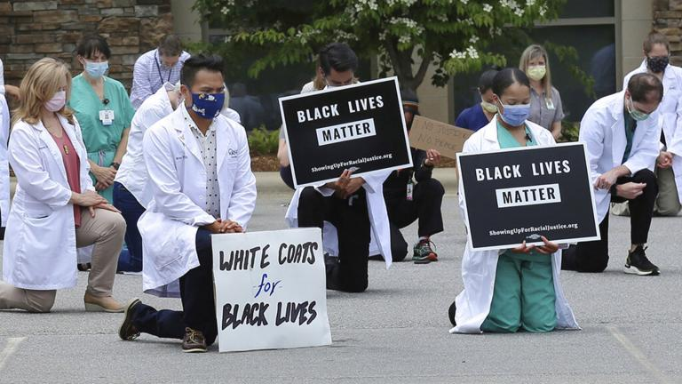 In this June 5, 2020 photo provided by the Mountain Area Health Education Center, physicians, residents and staff from the facility in Asheville, N.C., take a knee to show support for renewed calls for racial justice after the police killing of George Floyd. (Brenda Benik / MAHEC via AP)