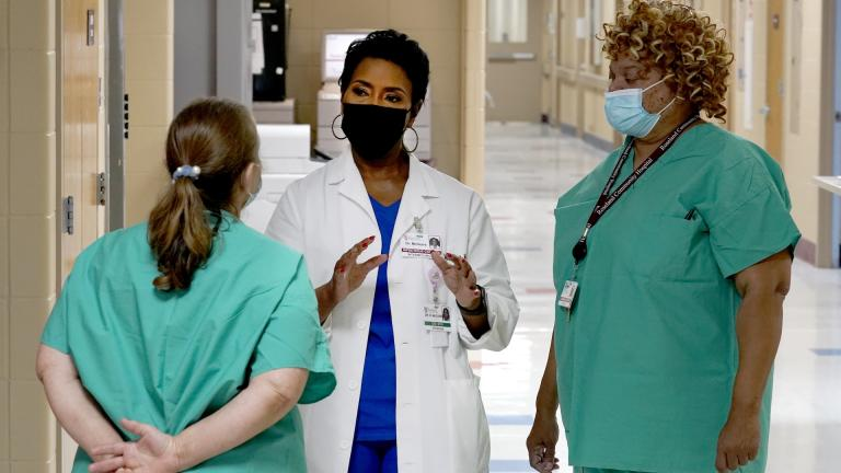 Dr. Rita McGuire, an obstetrician and infection control specialist at Roseland Community Hospital talks Friday, Jan. 29, 2021, with staff members about taking the COVID-19 vaccine. (AP Photo/Charles Rex Arbogast)