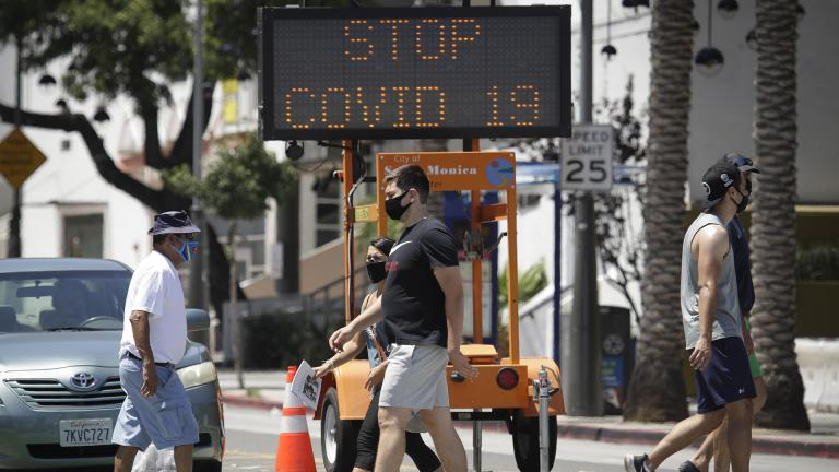 Pedestrians wear masks as they cross a street amid the coronavirus pandemic Sunday, July 12, 2020, in Santa Monica, Calif. (AP Photo / Marcio Jose Sanchez)